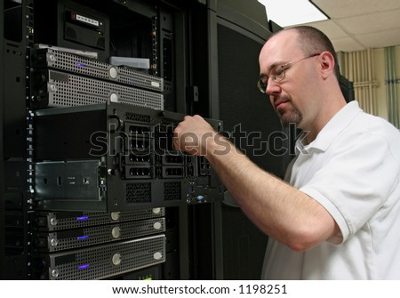 Computer Technician working on a server. - stock photo