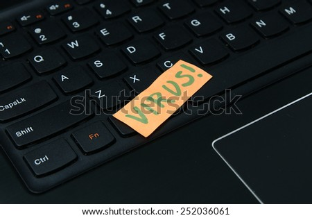 Computer virus warning. Sticky notes on the laptop keyboard with the word 'VIRUS'