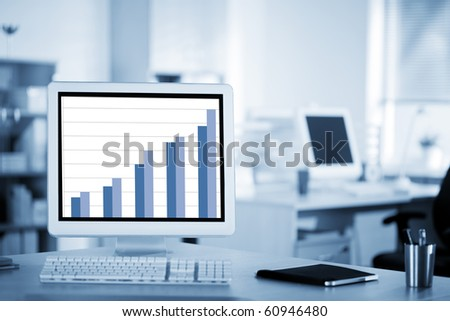 Computer with a business graph on screen on the working place in the office