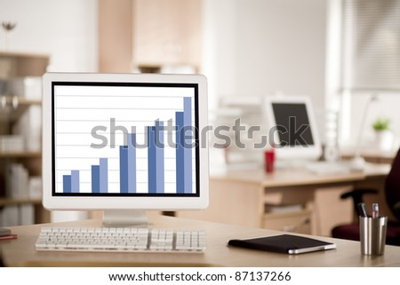 Computer with a business graph on screen on the working place in the office - stock photo