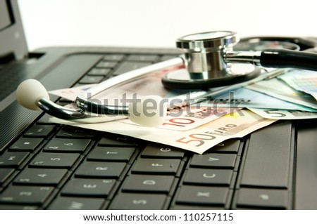 Computer with stethoscope and money