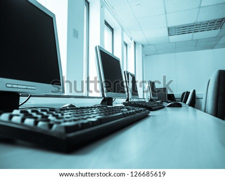 Computers in an office with light from windows.