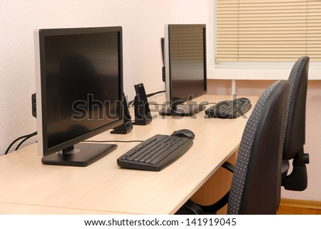 Computers on tables in room