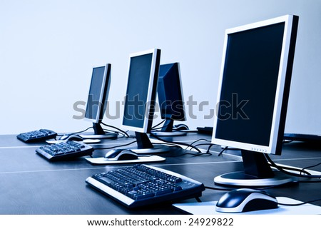computers with LCD screens blue toned - stock photo