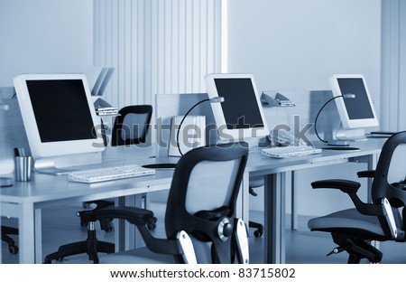 Computers with LCD screens in modern office in the blue tilt - stock photo