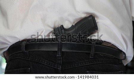 Concealed Weapon/Close view of black automatic pistol tucked into man's belt from behind - stock photo