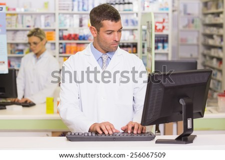 Concentrate pharmacist using computer at the hospital pharmacy - stock photo