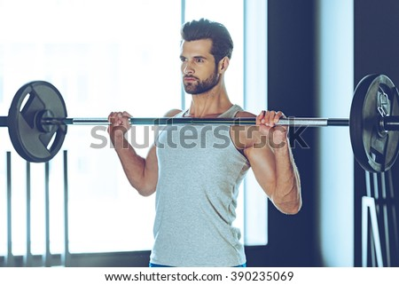 Concentrated and strong. Young handsome man in sportswear lifting barbell at gym - stock photo