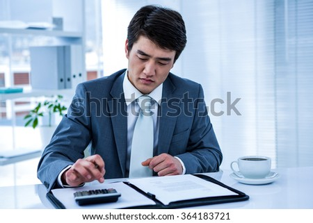 Concentrated asian businessman use calculator in his office - stock photo