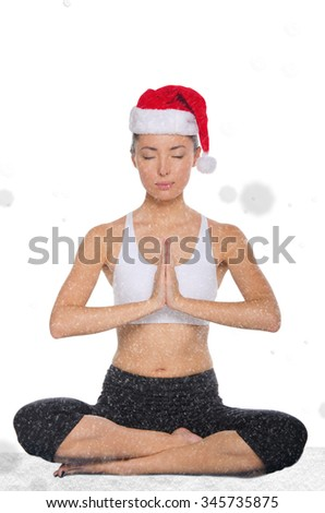 concentrated asian woman in christmas hat with snow practicing yoga isolated on white - stock photo