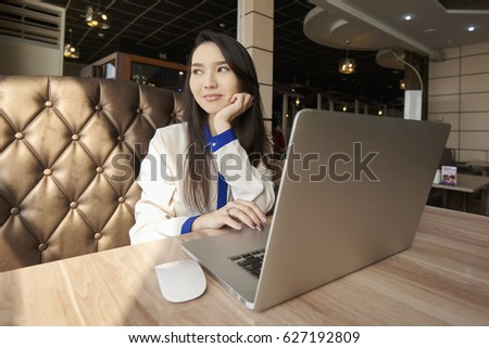 Concentrated asian young female office manager resting in cafe drinking favorite coffee during work break preparing for business meeting