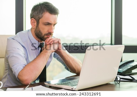 Concentrated at work. Confident mature man in shirt and tie looking at his laptop while sitting at his working place - stock photo