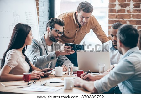 Concentrated at work. Group of five young people discuss something and gesturing while leaning to the table in office - stock photo