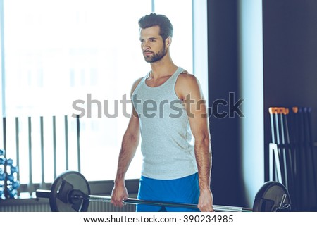 Concentrated athlete. Young handsome man in sportswear lifting barbell at gym - stock photo