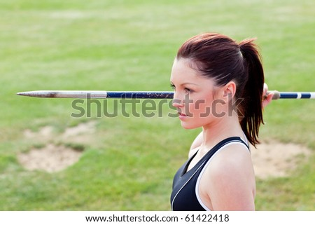 Concentrated athletic woman ready to throw the javelin in a stadium - stock photo