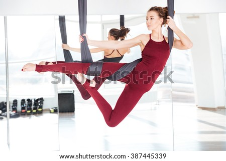Concentrated beautiful young woman practicing different antigravity yoga positions over the mirror - stock photo