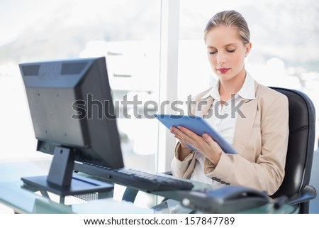 Concentrated blonde businesswoman in bright office using tablet