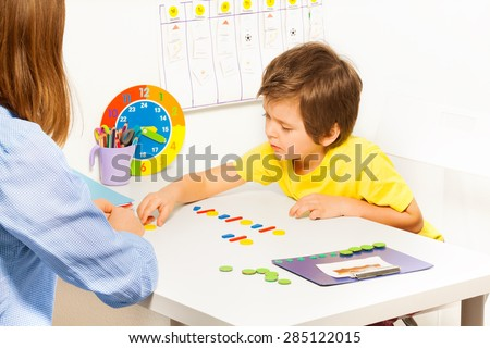 Concentrated boy puts colorful coins during ABA - stock photo