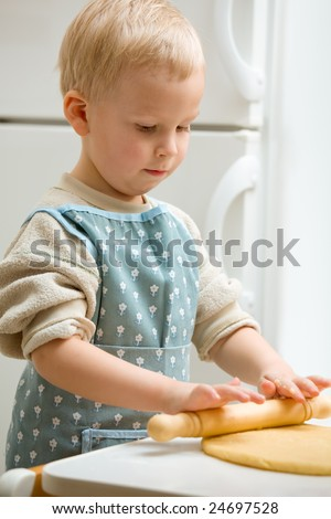 Concentrated boy roll out the dough in the kitchen