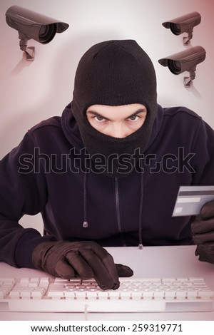 Concentrated burglar in balaclava shopping online against cctv camera - stock photo