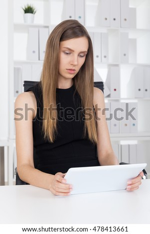 Concentrated business lady in black dress is looking at her huge tablet screen developing business strategy for the year. Concept of hard work