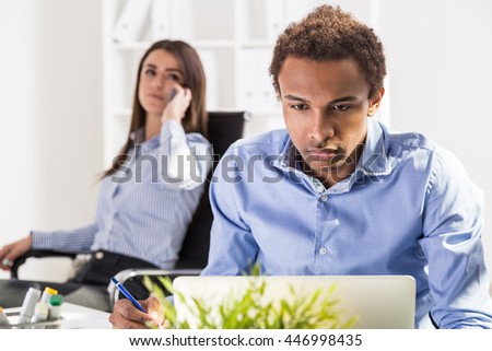 Concentrated business man and woman working on business project and having conversation on mobile phone. Concept of teamwork. Office interior in the background - stock photo