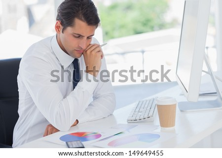 Concentrated businessman analyzing graphs in his office - stock photo
