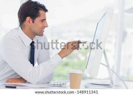 Concentrated businessman in his office analyzing documents on his computer screen - stock photo