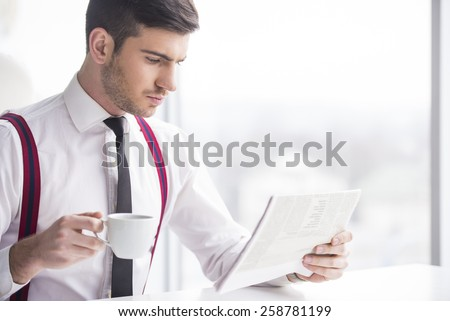 Concentrated businessman is analyzing documents and drinking coffe in his office. - stock photo