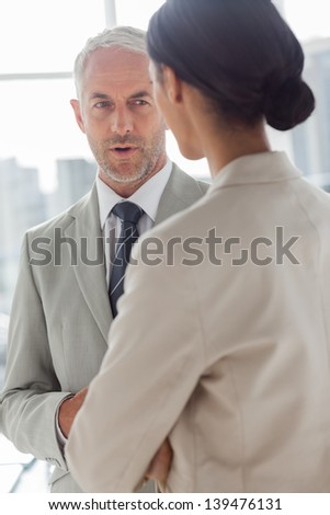 Concentrated businessman listening to female colleague in the office - stock photo