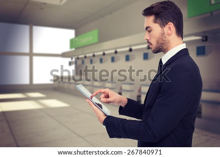 Concentrated businessman touching his tablet against airport
