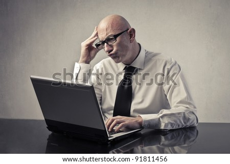 Concentrated businessman using a laptop - stock photo