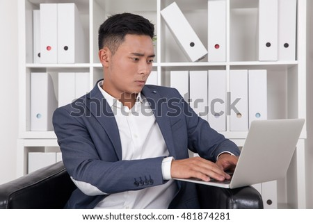 Concentrated businessman working at his laptop sitting in his large comfortable armchair. Concept of management work