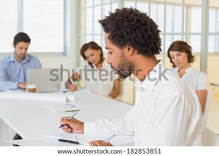 Concentrated businessman writing document with colleagues in meeting in background at the office