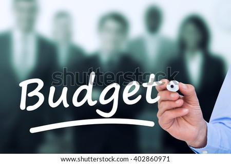 Concentrated businessman writing with marker against confident business team looking at the camera - stock photo