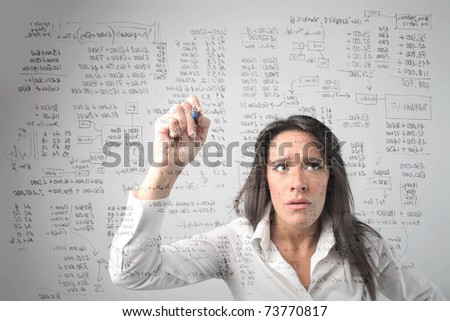 Concentrated businesswoman solving some complicated calculations - stock photo