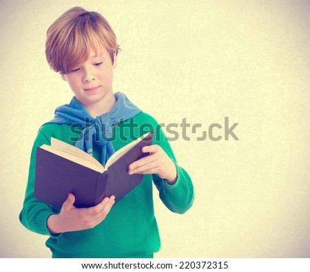 Concentrated child reading a book - stock photo