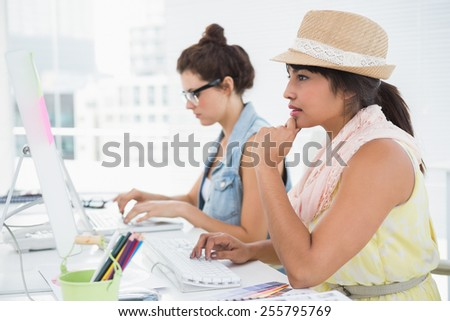 Concentrated colleagues typing on keyboard in the office - stock photo