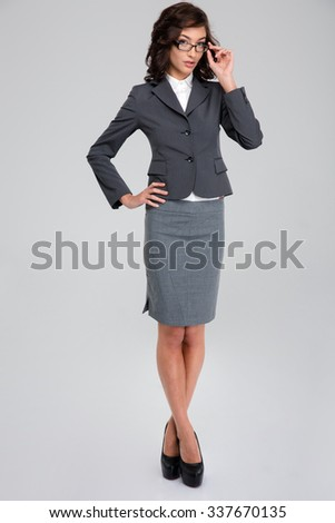 Concentrated confident curly pretty business woman in glasses and gray suit standing crossing legs and touching her glasses - stock photo