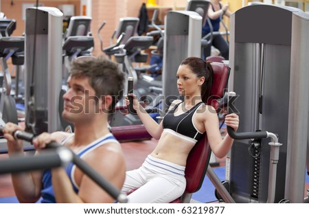 Concentrated couple using shoulder press in a fitness centre - stock photo