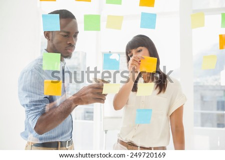 Concentrated coworkers looking at sticky notes in the office - stock photo