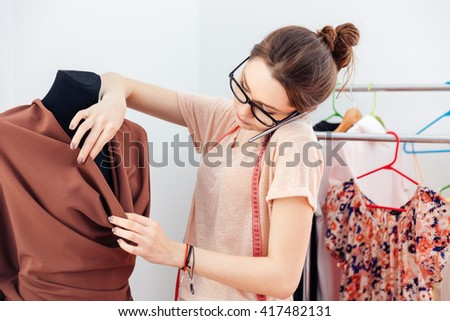 Concentrated cute young woman fashion designer creating new clothes and talking on cell phone - stock photo