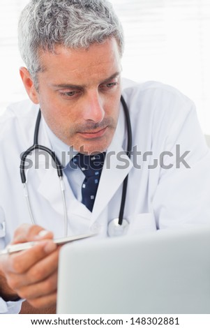 Concentrated doctor watching something on his laptop in medical office - stock photo