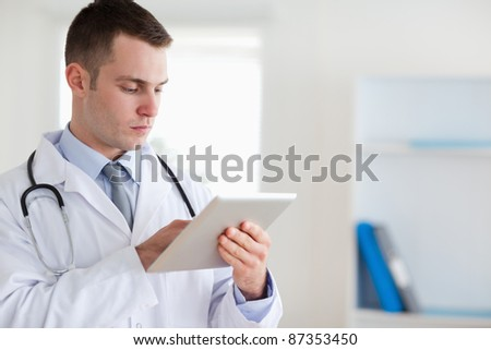 Concentrated doctor with tablet - stock photo