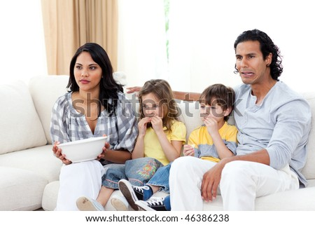 Concentrated family watching TV on sofa in the living room