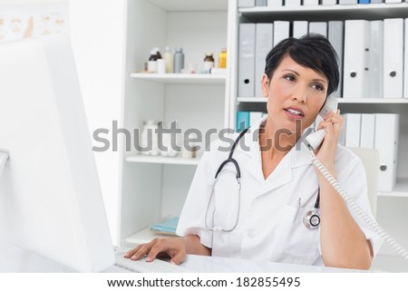 Concentrated female doctor using computer and telephone at medical office - stock photo
