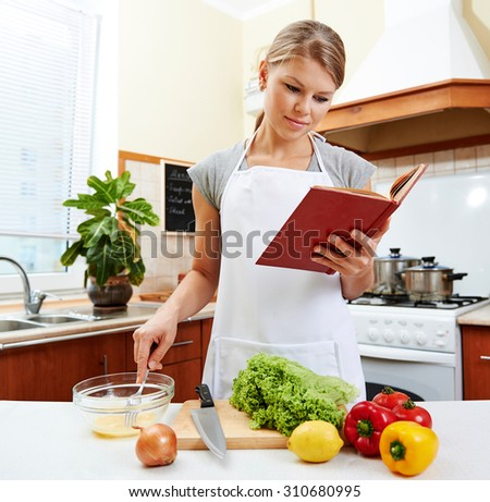 Concentrated female reading recipe book and cooking meal. Young housewife wearing white apron preparing vegetable dish in the house.