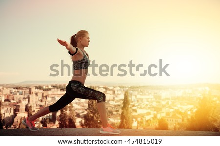 Concentrated fitness woman practicing yoga on mountain peak at sunset. Concept of healthy lifestyle and tranquility.  - stock photo