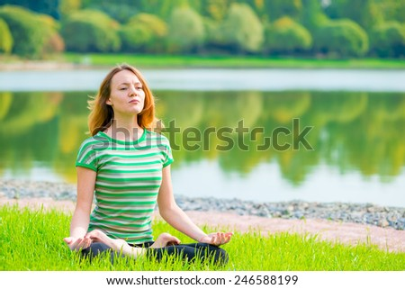concentrated girl in lotus position doing yoga on the nature - stock photo