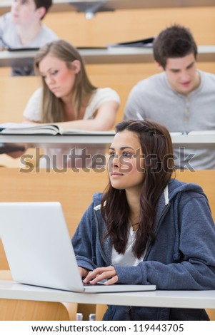 Concentrated girl sitting at the lecture hall with her laptop - stock photo